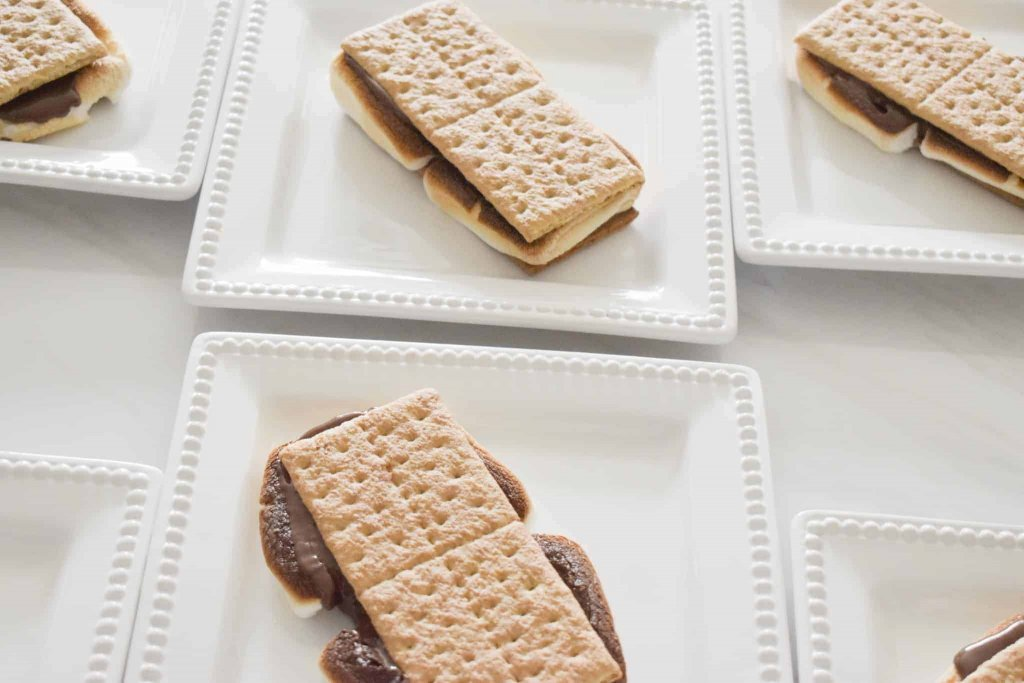 White square plates with s'mores on each one