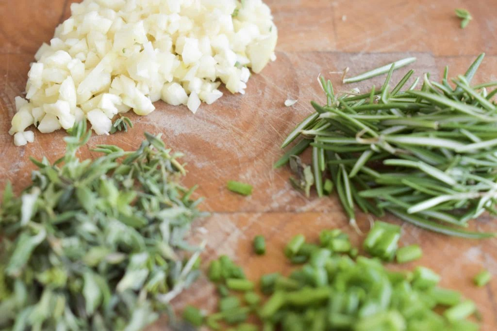 Photo of chopped garlic and fresh rosemary, chives and thyme on a cutting board
