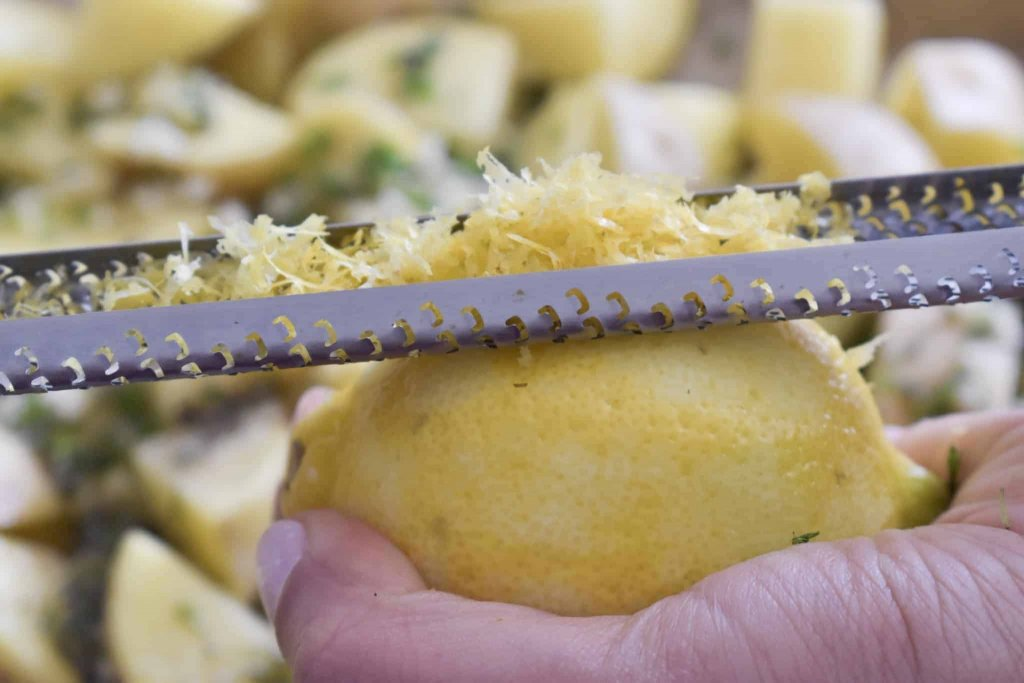 a photo showing how to zest a lemon with a rasp grater
