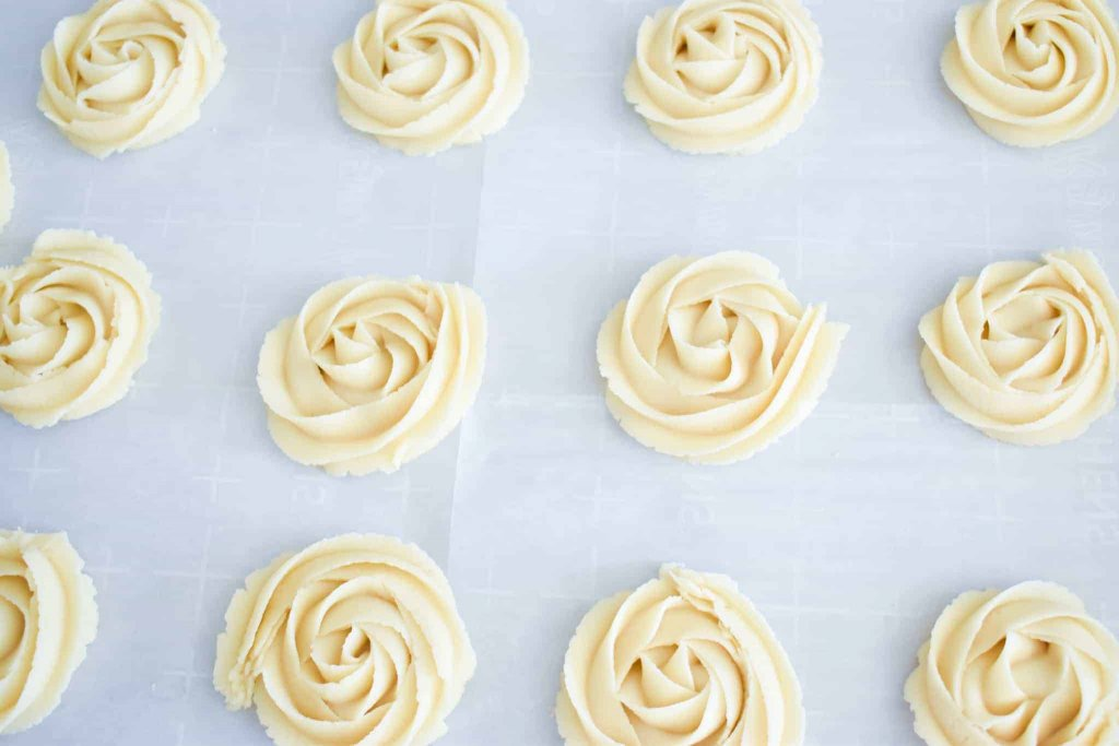 a baking sheet full of piped butter rosettes before baking