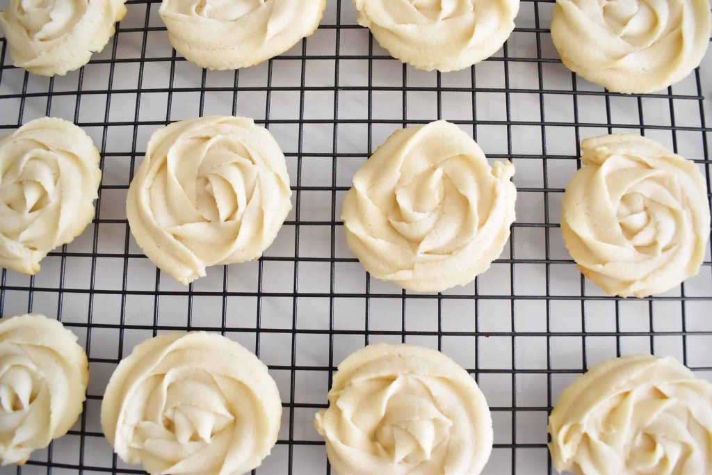 a wire rack full of piped butter rosettes after baking