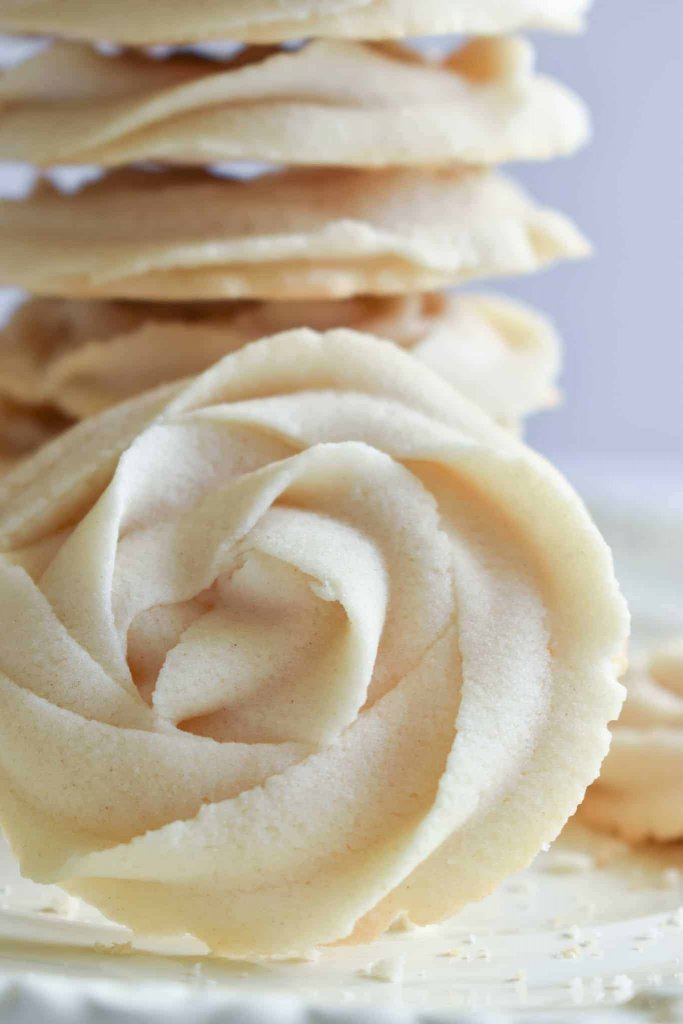 whipped rosette butter cookies stacked on top of each other with one cookie in the front
