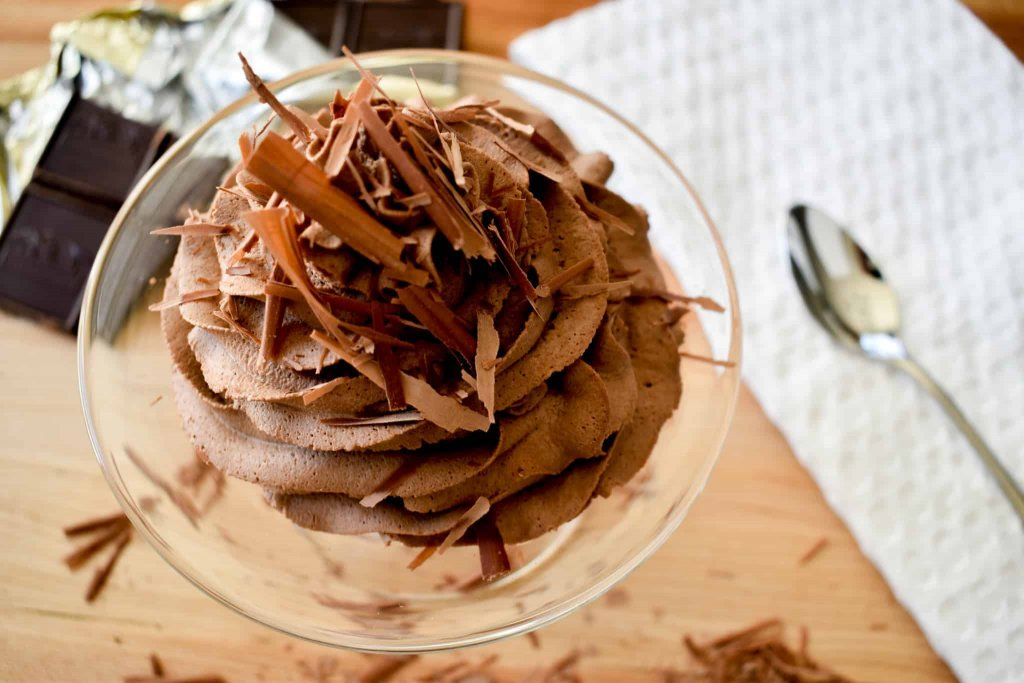 Chocolate whipped cream in a glass bowl  on a table with open chocolate bar, spoon and white napkin