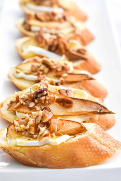 brie cheese with pear and pecan crostini with honey served on a white plate