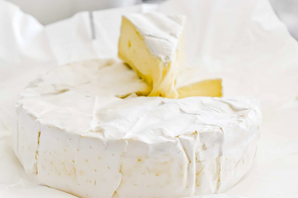 photo of a whole Brie Cheese circle with a piece  of Brie Cheese sliced on top