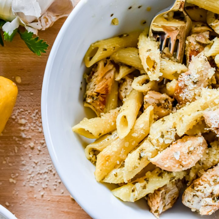 A bowl of lemon chicken pasta with a lemon parsley and garlic near it