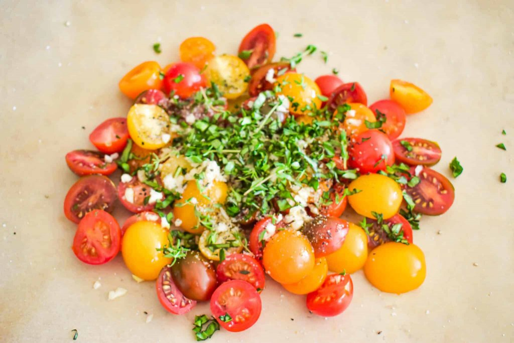 cherry tomatoes, herbs, garlic and olive oil on parchment paper prior to roasting