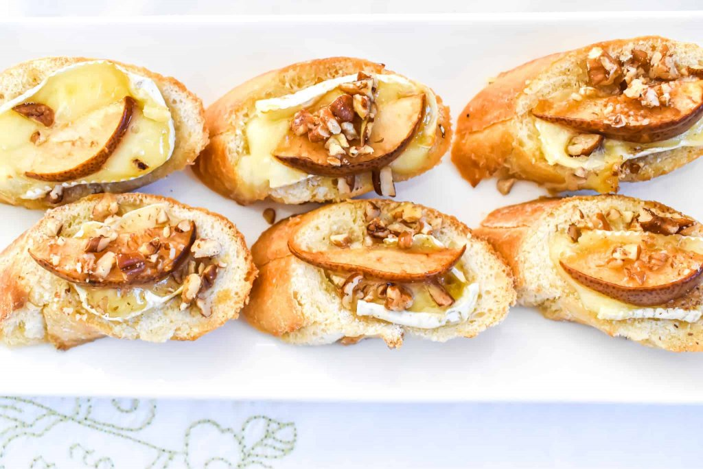 Brie Cheese with pear, pecan and honey crostini served on a white plate