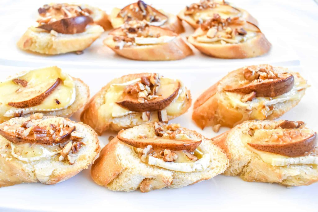 brie cheese with pear and pecan and honey crostini  served on a white plate